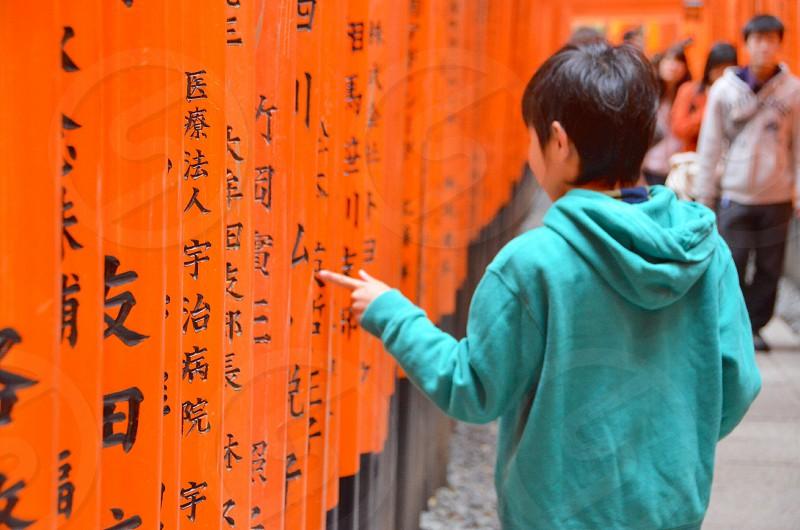 child in green hooded sweatshirt walking past orange painted poles photo