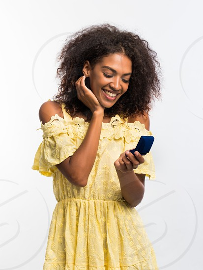 Young beautiful african american woman enjoying and dancing at white background. Modern trendy girl with afro hairstyle listening to music by wireless portable speaker photo