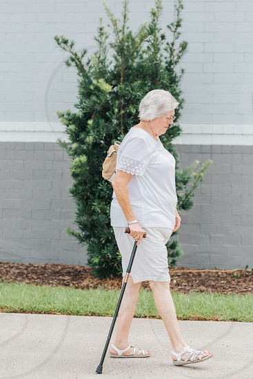 Elderly woman walking with a cane photo