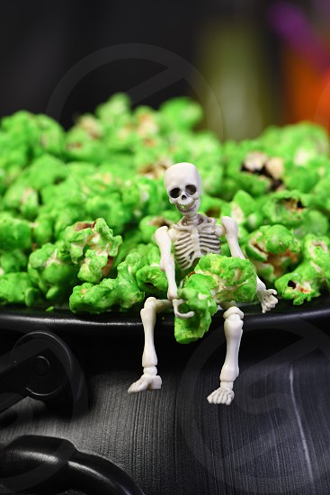 A skeleton sits on the edge of a cauldron and holds in its hands a green sweet popcorn. Close-up. Halloween treats. photo