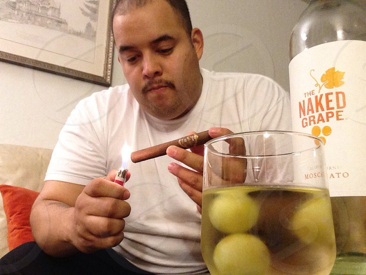 Lighting up a Tatuaje cigar and drinking the naked grape wine photo