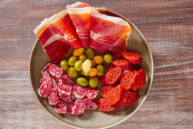 Tapas of Spain with ham olives sausage and chorizo on wooden background photo