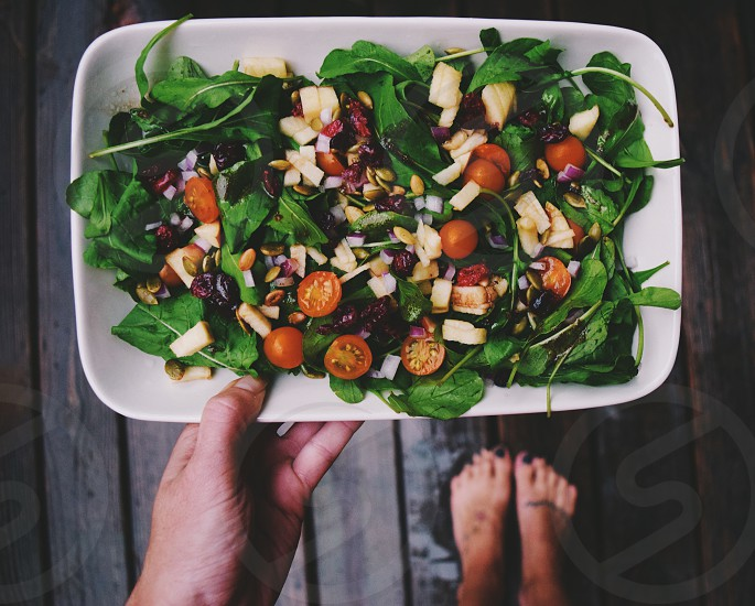 person holding a white plate with a spinach salad cherry tomatoes and chopped apples photo