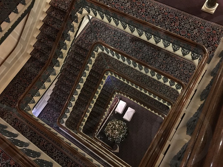 photo of square-form stairs with brown-and-green floral area rugs photo