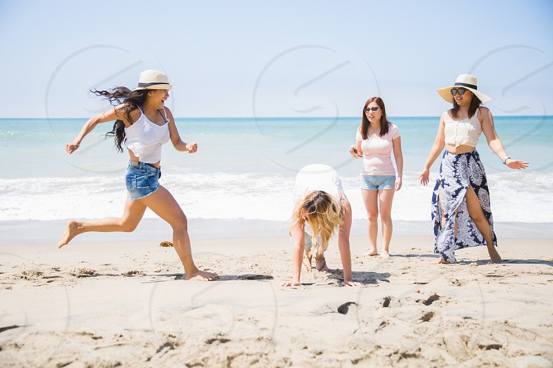 4 woman on white sand near clear sea water photo