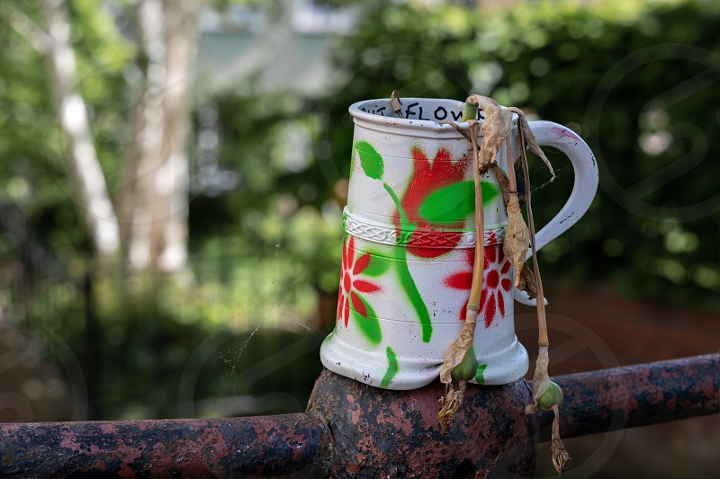 Old dented and painted tankard containing dead daffodils photo