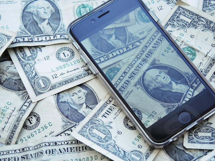 black i phone on top of one dollar bills photo