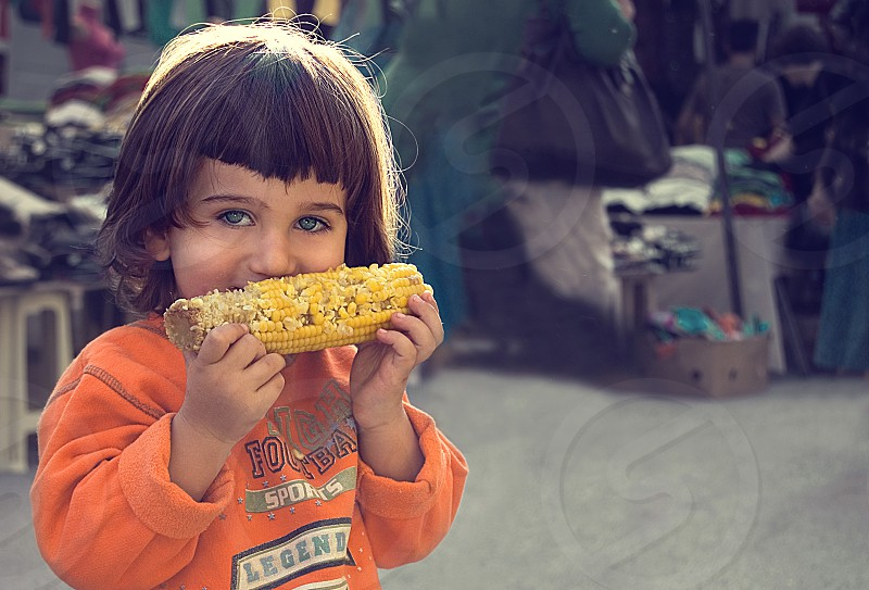 A girl happily eating corn. photo