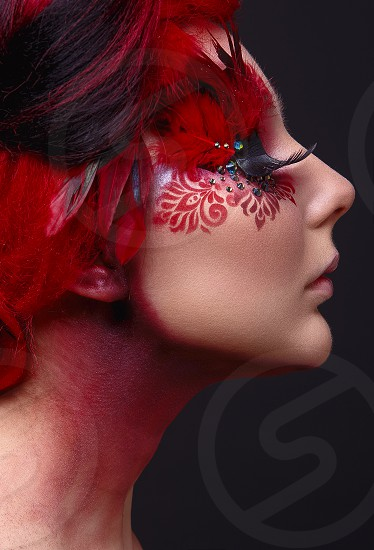 Portrait of a beauty young  girl with red hair.  Creative ingenious makeup with feathers rhinestones and large eyelashes photo