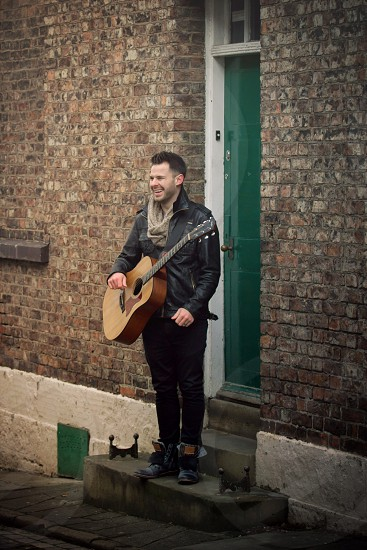 man in black leather jacket and black pants with brown acoustic guitar by doorway photo