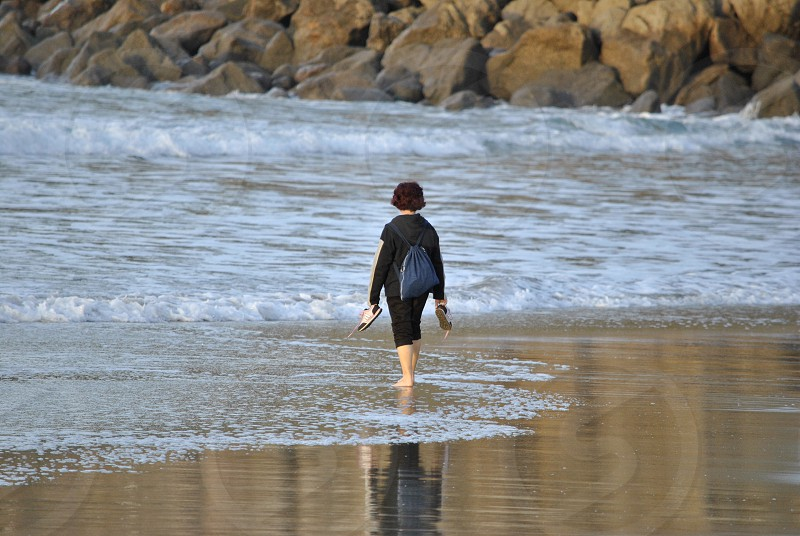 woman walking barefooted at the beach photo