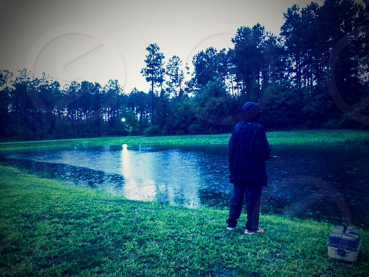 TWELVE years old boy FISHING in RAIN photo