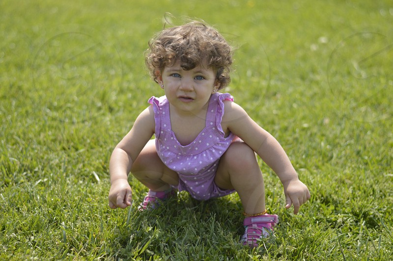 Girl purple blue eyes white dots grass outdoors curly hair photo