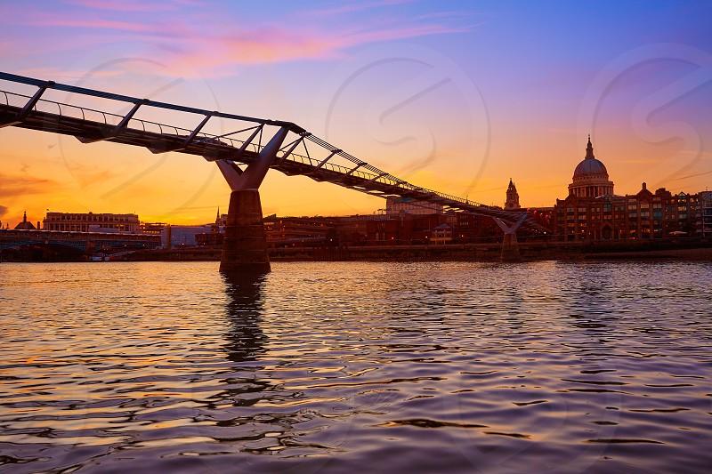 London Millennium bridge sunset skyline in UK at dusk photo
