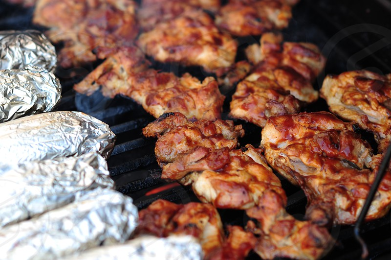 grilled meat with a brown color beside an aluminum foil wrap on grill photo