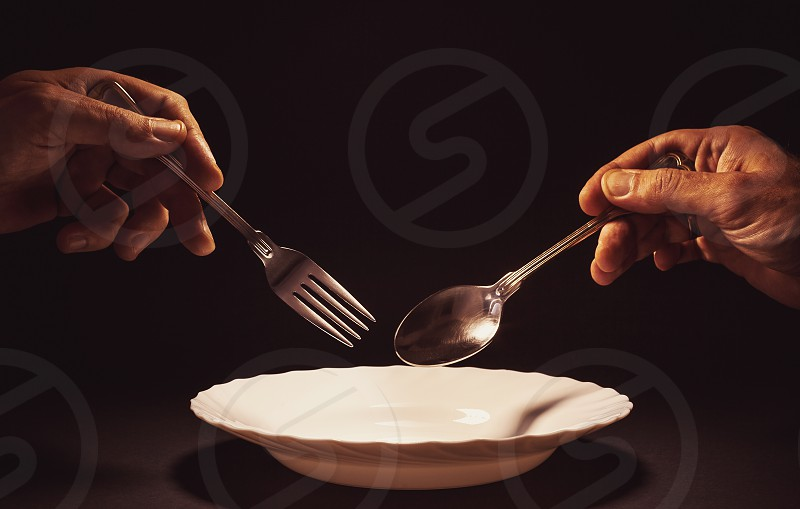 Conceptual composition man's hand holding a metal spoon and fork over the empty white plate. Issue about no food and poverty and similar. photo