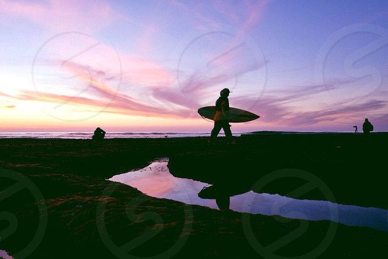 person walking with surfboard along coast with sun setting  photo