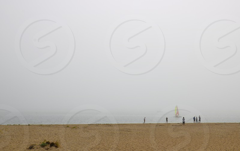 Tiny people walk on the sandy shore near the ocean  under a Hazy foggy sky photo