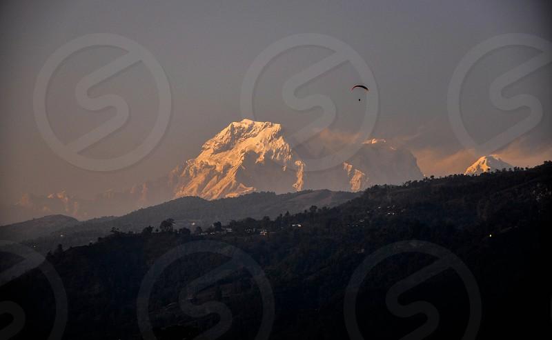 Paragliding snowy mountains snow sunshine sunset evening himalaya adventure silhouette photo