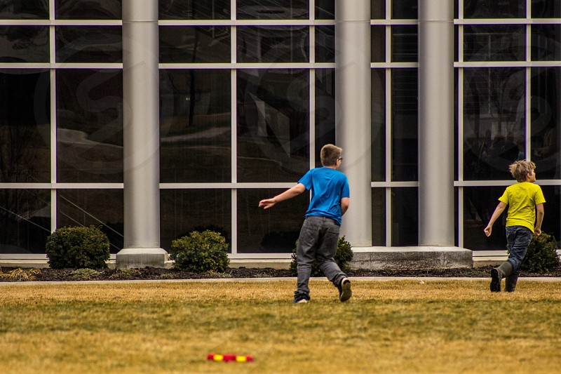 toddler boy wears blue t-shirt on grass field during daytime photo