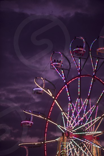 Ferris wheel at amusement park state fair with lights at night photo