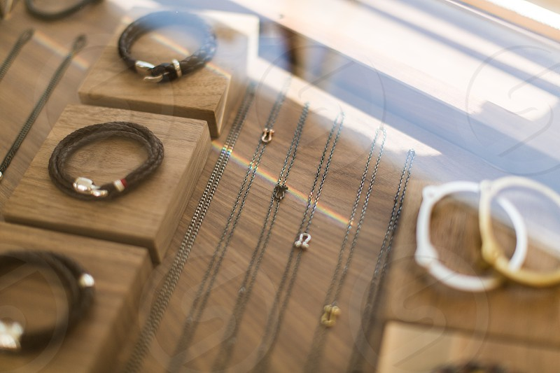 leather bracelets and jewelry behind a glass case. reflections glass natural light sunlight gold silver leather pretty photo