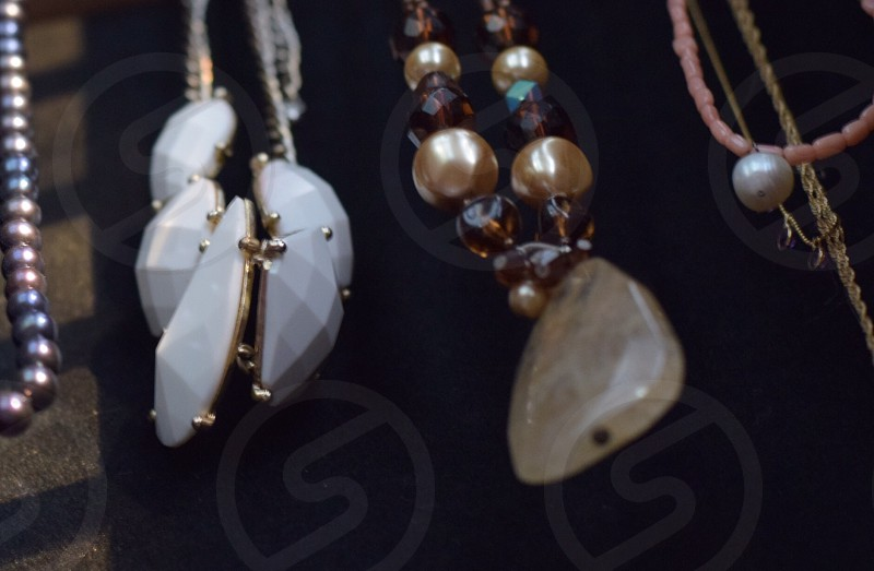 silver and gold beaded necklaces hanging in a row photo