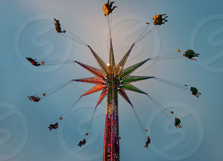 low angle photography of people riding spinning drop tower amusement park ride under blue sky at daytime photo