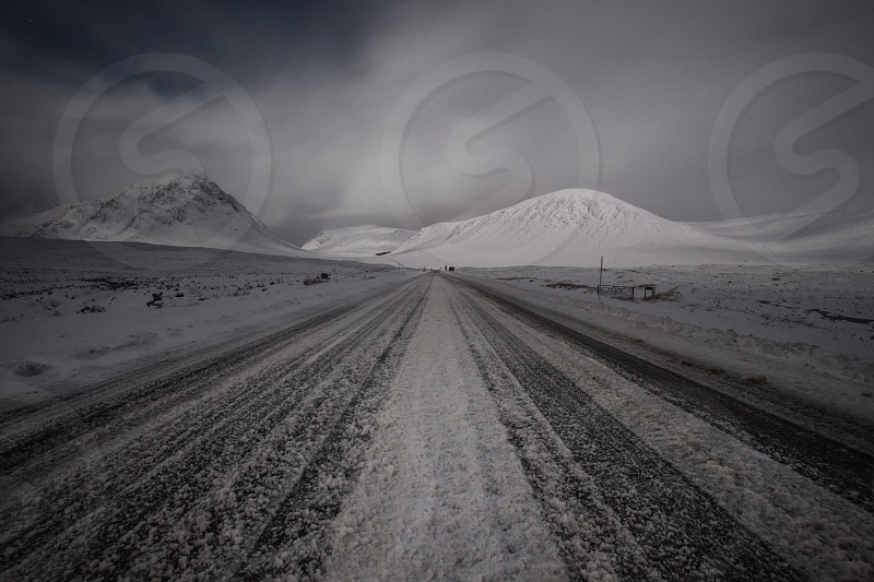 snow covered pathway through snow covered mountains under cloudy skies photo