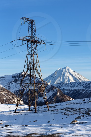 High voltage power line at winter sunny day. View on high voltage metal tower in mountain on background of snow-capped cone of Vilyuchinsky Volcano. Kamchatka Peninsula Russian Far East Eurasia. photo