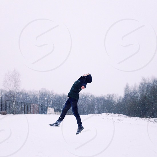 woman levitates above snow covered field photo