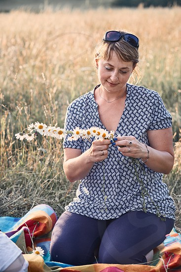 Smiling happy woman making coronet of wild flowers. Family spending time together on a meadow close to nature. Candid people real moments authentic situations photo