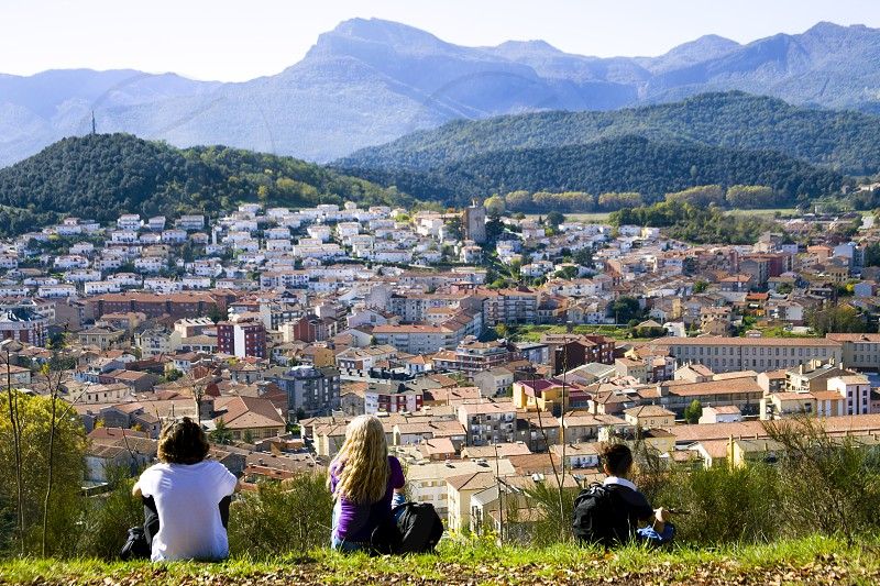 A view of the city of Olot and the Garrocha volcanic park from the top of the Montsakopa volcano. The family rests after hiking and admires the beautiful views. photo
