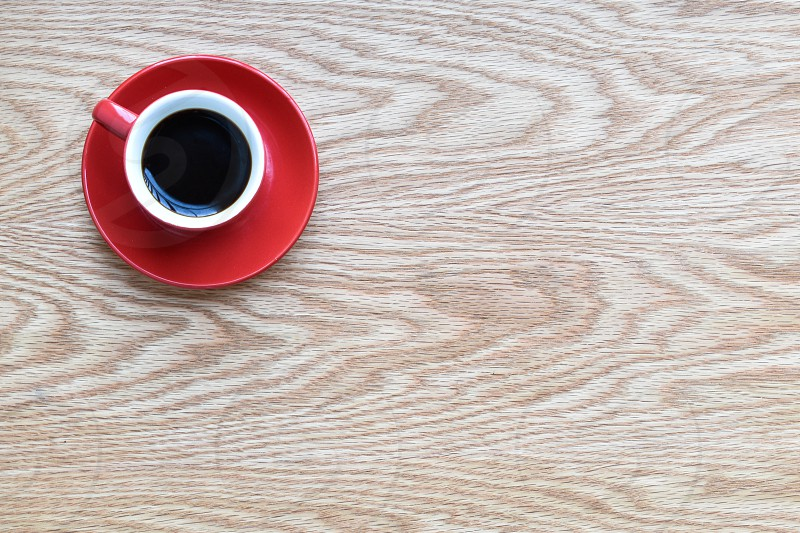 Top viewBlack coffee in red cup on wooden table photo