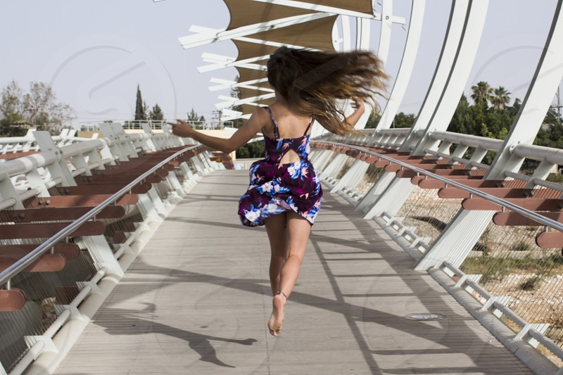 woman in maroon and blue floral spaghetti strap dress standing on bridge photo