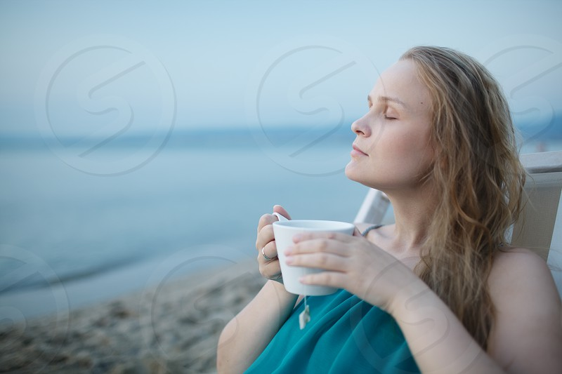 Woman with closed eyes enjoying a cup of tea at the seaside sitting relaxing on a deckchair with a blissful expression overlooking a tropical beach photo