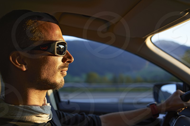 Side profile of a caucasian man driving towards the sunrise to go trekking in the mountains photo