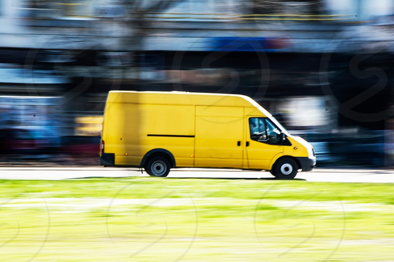Yellow van in full speed in a city traffic photo