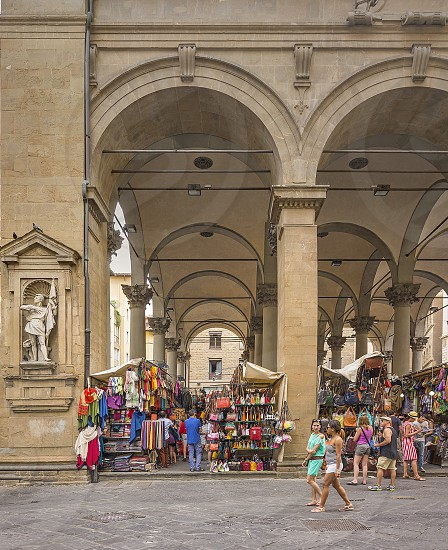 Florence Italy June 2015: tourists and Florentines walking and shopping in the historic Mercato del Porcellino (pig market) in the center of Florence with Tuscan leather goods photo