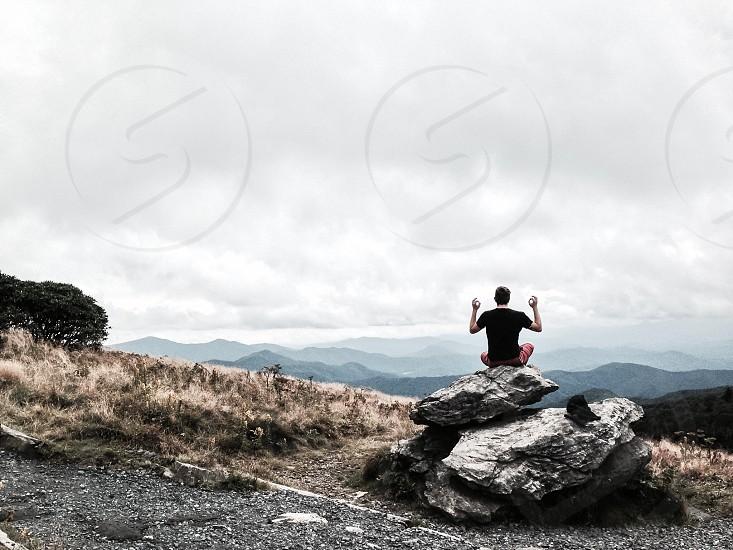 man wearing black t-shirt sitting on rock overlooking mountains photo
