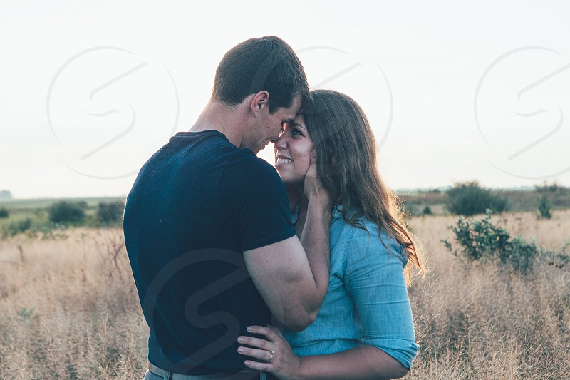 man in black polo shirt and woman in blue long sleeve button up shirt standing on brown grass field photo