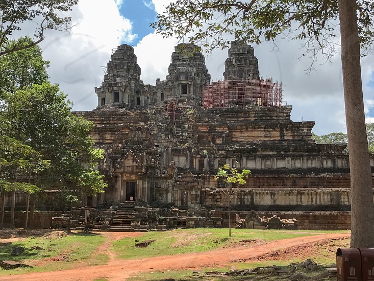 Outdoor day colour landscape horizontal Angkor Angkor National Park Siem Reap Cambodia Asia Asian east eastern ancient holy spiritual Khmer dynasty monument sky blue white clouds summer travel tourism tourist wanderlust stone carved ornate elaborate figure figures temple grounds ruin ruined trees photo