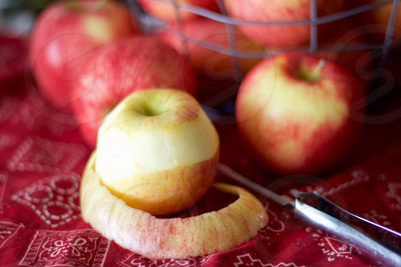 Gala apples in a wire basket with a partially peeled apple and peeler on a red bandana-print tablecloth photo