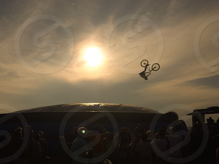 person riding bicycle doing front flip trick in mid air photo