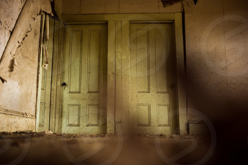 Two pale green doors in a long abandoned house. photo