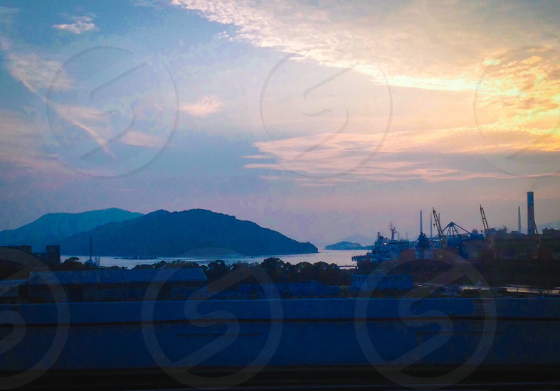 A view from a train in Japan. Yiu can see mountains and the sun begin to set photo