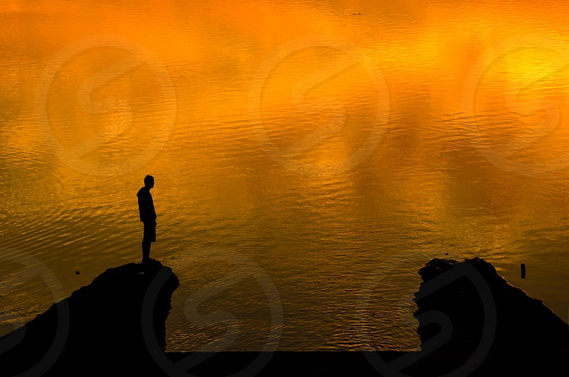 Lonely man over water during sunset. photo