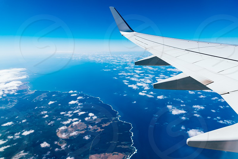 Wing of airplane above island. Traveling concept photo