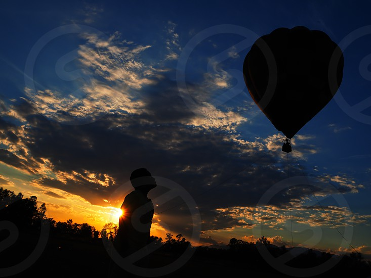silhouette hot air balloon and young people in evening twilight sunset sky scape background concept of motivation and inspiration photo