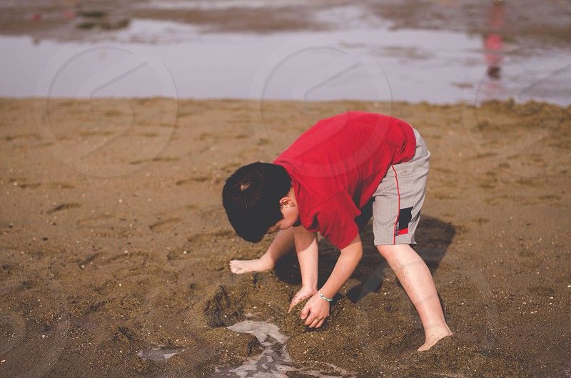 boy in red playing on sand photo